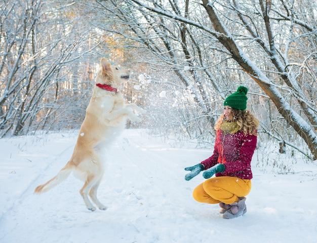 Heureuse belle jeune femme soufflant des flocons de neige de ses mains à son chien