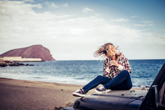Heureuse belle jeune fille blonde rester en plein air en profitant du temps et du voyage avec une voiture noire hors route