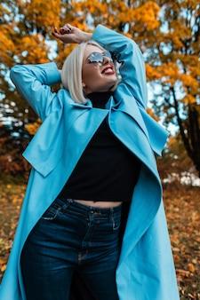 Heureuse belle jeune fille avec des lunettes de soleil dans un manteau bleu à la mode avec un pull noir et un jean dans la forêt sur fond de feuillage d'automne jaune