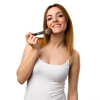 Heureuse belle jeune fille avec un pinceau de maquillage