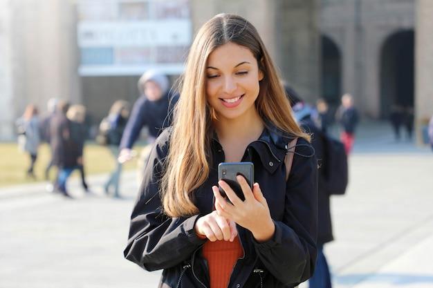 Heureuse belle jeune lycéenne avec téléphone intelligent à l'extérieur le jour de printemps ensoleillé textos et souriant