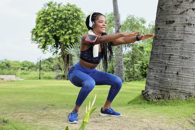 Heureuse belle jeune sportive noire dans les écouteurs faisant des squats dans le parc après la course du matin