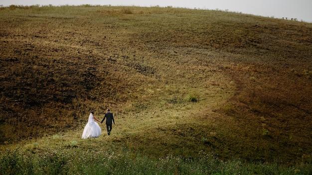 Heureuse belle mariée et le marié marchant sur le terrain au soleil