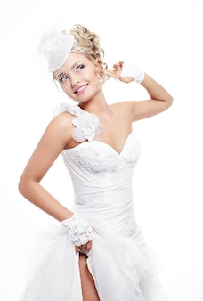 Heureuse belle mariée souriante en robe de mariée blanche avec coiffure et maquillage lumineux