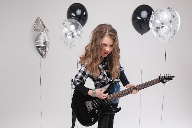 Heureuse belle petite fille artistique jouant de la guitare