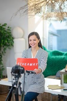 Heureuse blogueuse debout devant la caméra tout en tenant une pancarte cadeau