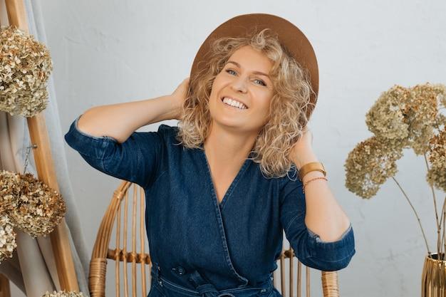 Heureuse blonde frisée souriante au chapeau sur fond clair parmi un décor naturel de fleurs séchées, souriant largement à la caméra avec un sourire blanc. stock photo
