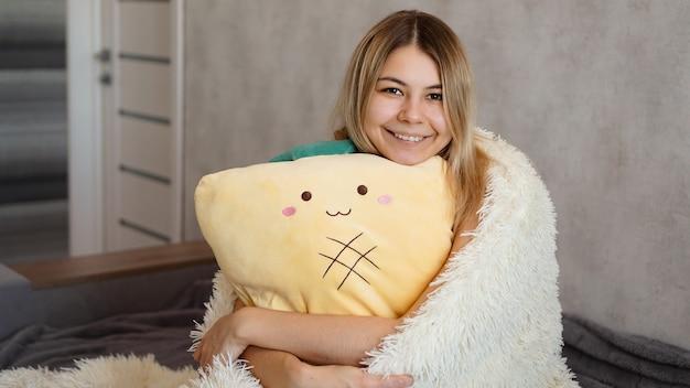 Heureuse blonde sous une couverture blanche le matin embrasse un oreiller jaune. concept de bon matin