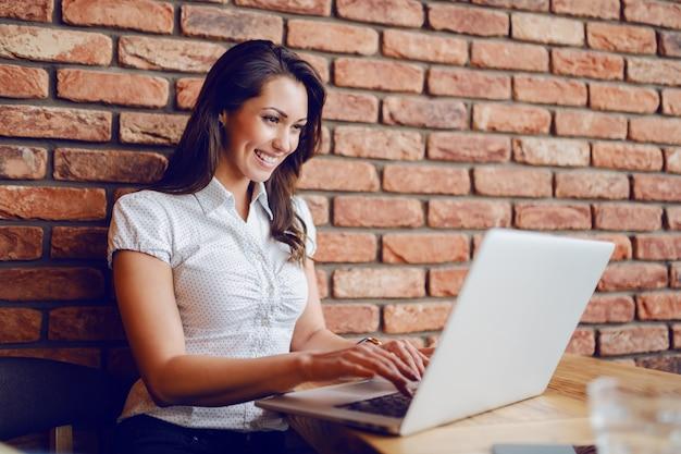 Heureuse brune assez caucasienne assis dans un café et à l'aide d'un ordinateur portable. les mains sont sur le clavier. en arrière-plan, un mur de briques.