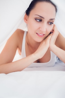 Heureuse brune couchée sous les draps en détournant les yeux