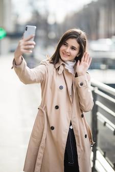 Heureuse brune souriante a un appel vidéo sur son téléphone à l'extérieur