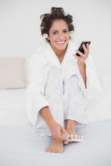 Heureuse brune souriante, application de vernis à ongles aux orteils et textos