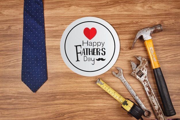 Heureuse carte de fête des pères avec de vieux outils rouillés et une cravate sur fond en bois