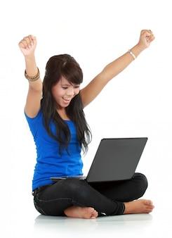 Heureuse et chanceuse jeune femme avec ordinateur portable