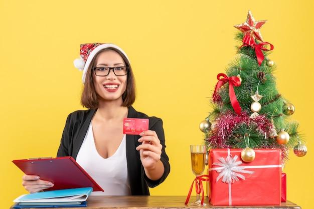 Heureuse charmante dame en costume avec chapeau de père noël et lunettes montrant une carte bancaire au bureau