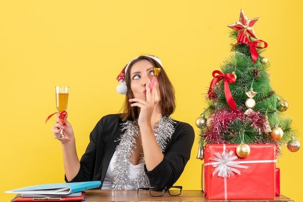 Heureuse charmante dame émotionnelle en costume avec chapeau de père noël et décorations de nouvel an élevant du vin au bureau sur jaune isolé