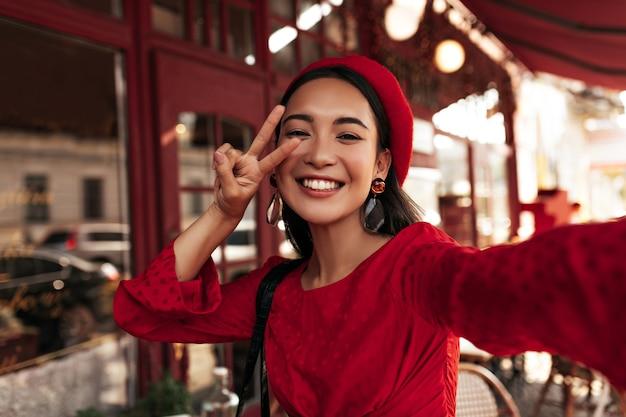 Heureuse charmante femme brune en robe rouge, béret élégant et lunettes sourit sincèrement, montre un signe de paix et prend un selfie à l'extérieur