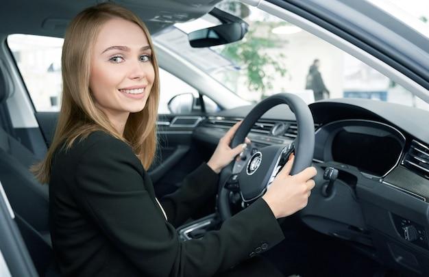 Heureuse cliente assise dans une nouvelle automobile confortable