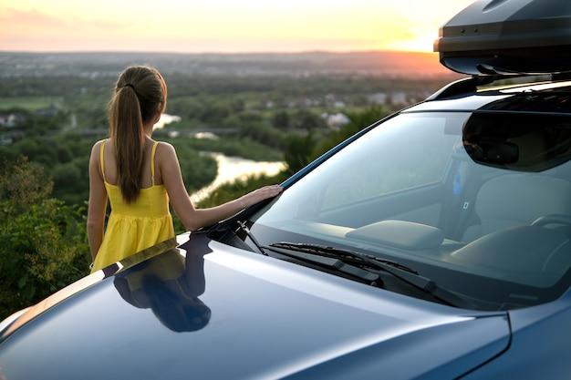 Heureuse conductrice en robe d'été profitant d'une soirée chaude près de sa voiture. concept de voyage et de vacances.