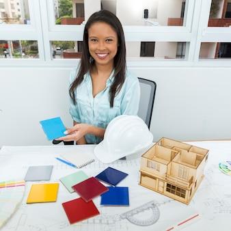Heureuse dame afro-américaine sur une chaise montrant le panneau de façade près du plan et du modèle de maison sur table