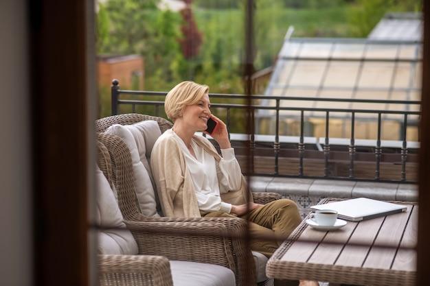 Heureuse dame d'âge moyen parlant sur le smartphone à l'extérieur