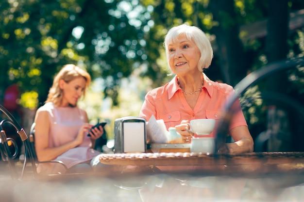 Heureuse dame âgée assise à l'extérieur à la table du café et regardant loin avec un sourire