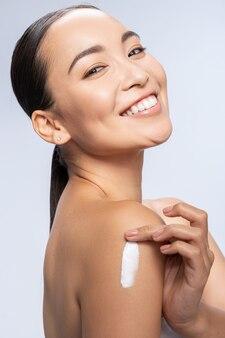 Heureuse dame asiatique frottant la lotion dans la peau