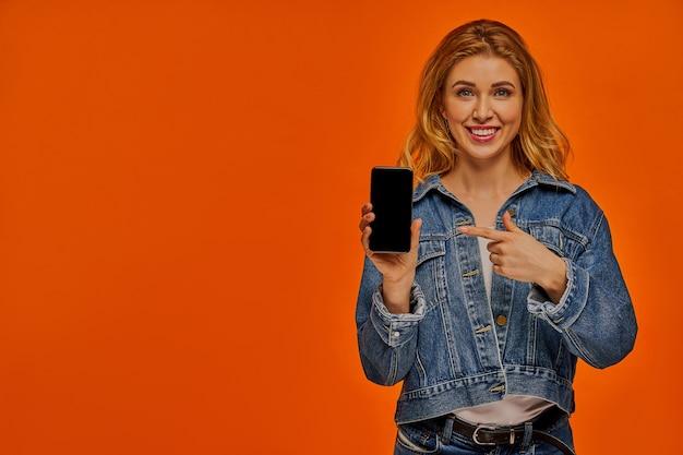 Heureuse dame aux cheveux blonds ondulés dans une veste en jean tient et pointe vers un téléphone dans sa main droite
