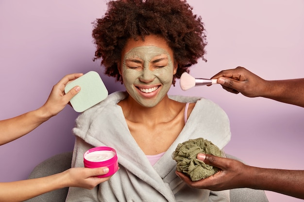 Heureuse dame aux cheveux bouclés en peignoir reçoit des traitements anti-âge et de beauté en même temps