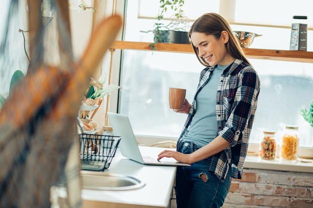 Heureuse dame buvant du thé dans la cuisine et utilisant son ordinateur portable