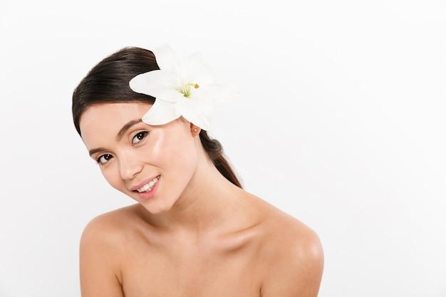 Heureuse dame avec fleur en tête et souriant isolé