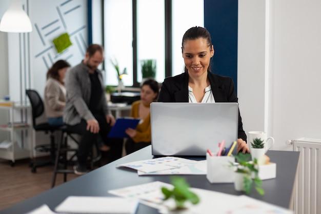 Heureuse dame hispanique tapant sur un ordinateur portable assis au bureau dans un bureau de démarrage en buvant du café pendant que divers collègues travaillent en arrière-plan