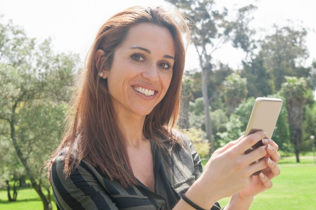 Heureuse dame joyeuse à l'aide d'un smartphone à l'extérieur