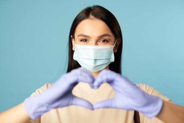 Heureuse dame en masque de protection et gants montrant la forme du coeur avec les mains