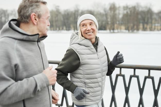 Heureuse dame mature sportive en gants et chapeau souriant au mari pendant qu'ils courent ensemble le long de la rivière dans le parc d'hiver