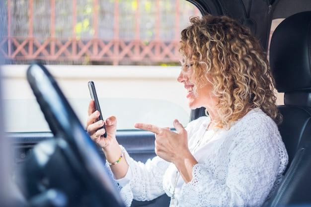 Heureuse dame parlant en vidéoconférence s'asseoir à l'intérieur de la voiture sur le siège passager tenant un téléphone et souriant à des amis - connexion en ligne internet personnes cellulaires