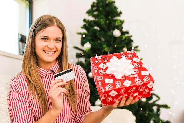 Heureuse dame tenant une boîte-cadeau et une carte de crédit près de sapin de noël