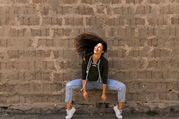 Heureuse danseuse de style moderne posant devant le mur