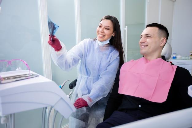 Heureuse dentiste et patiente examinant la radiographie des dents saines. prévention des caries, nettoyage des dents. un jeune homme se rend chez le dentiste.