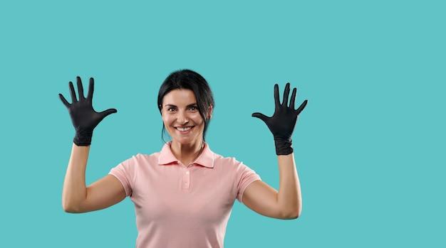 Heureuse et drôle jeune brune souriante et montrant ses mains dans des gants en latex médicaux noirs. image isolée sur fond bleu