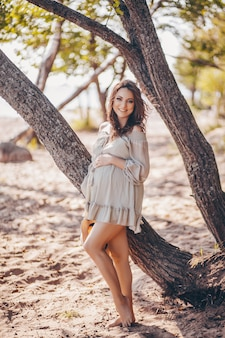 Heureuse élégante femme enceinte souriante posant sur la plage