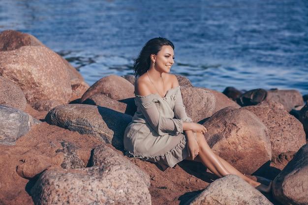 Heureuse élégante souriante jeune femme posant sur la plage