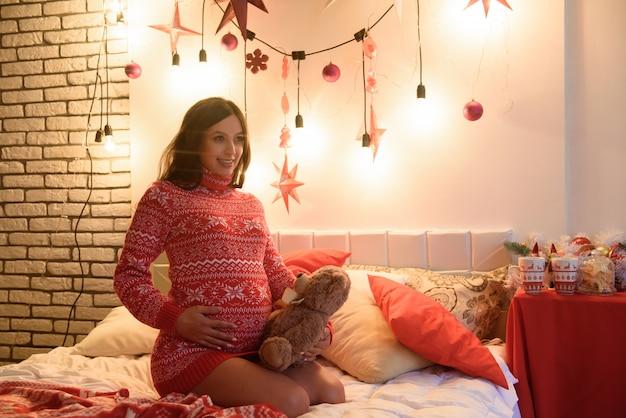 Heureuse enceinte sur le lit