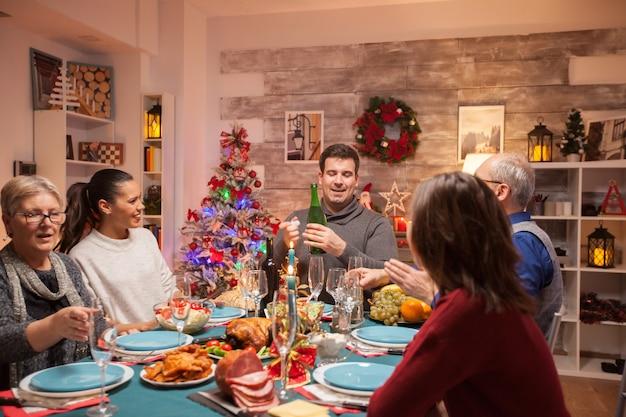 Heureuse épouse regardant son mari au dîner de noël en famille tout en ouvrant une bouteille de vin.