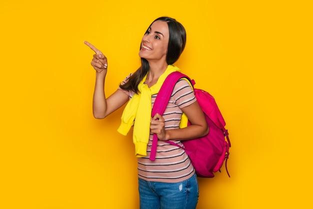 Heureuse étudiante mignonne dans des vêtements décontractés modernes avec un sac à dos rose pose en studio