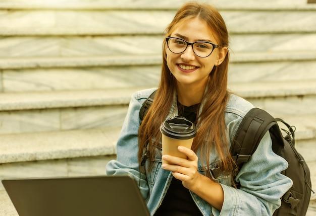 Heureuse étudiante moderne en veste en jean et sac à dos assis dans les escaliers avec ordinateur portable en plein air. boit du café. apprentissage à distance. concept de jeunesse moderne.