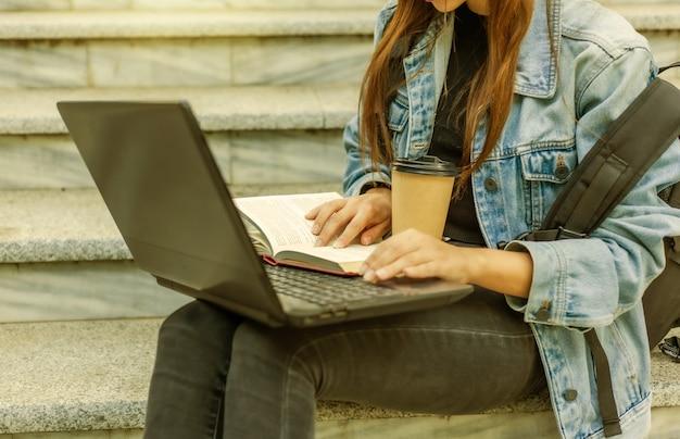 Heureuse étudiante moderne en veste en jean et sac à dos assis dans les escaliers et utilise un ordinateur portable avec un livre en plein air. apprentissage à distance. concept de jeunesse moderne.
