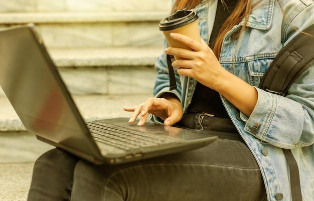 Heureuse étudiante moderne en veste en jean et sac à dos assis dans les escaliers et utilise un ordinateur portable en plein air. boit du café. apprentissage à distance. concept de jeunesse moderne.