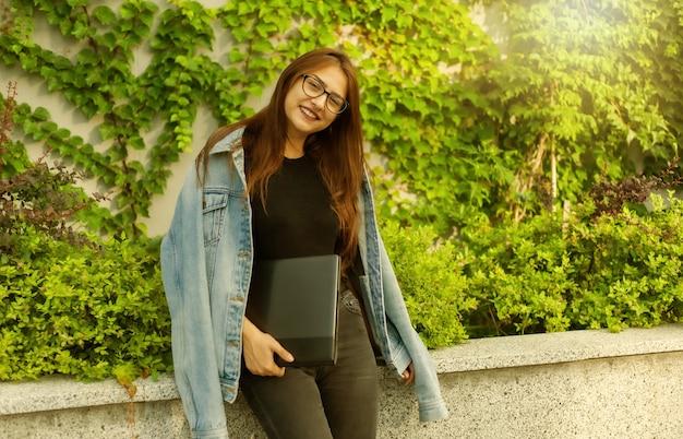 Heureuse étudiante en veste en jean et lunettes avec ordinateur portable dans les mains dans la ville