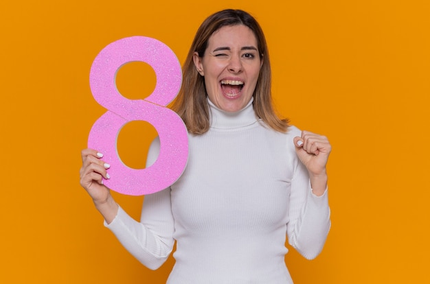 Heureuse et excitée jeune femme en col roulé blanc tenant le numéro huit en carton